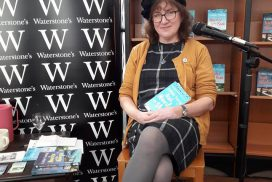Debbie Young with her books in bookstore with Waterstones brand clearly visible