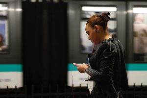 woman listening to something through headphones on her smartphone