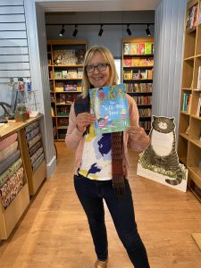Karen holding a copy of her book in a store